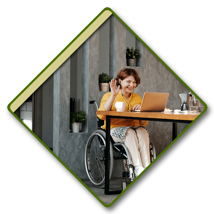 Young woman in a wheelchair using a laptop with headphones.
