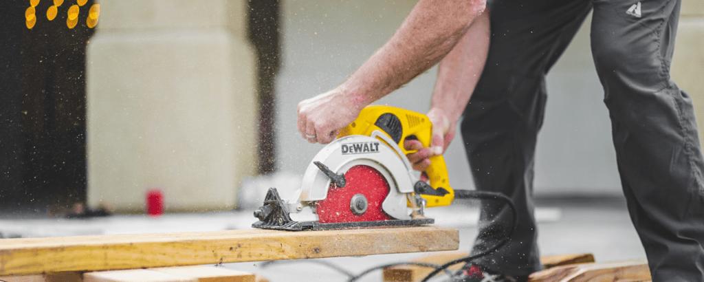 man cutting wood using a round wood cutter