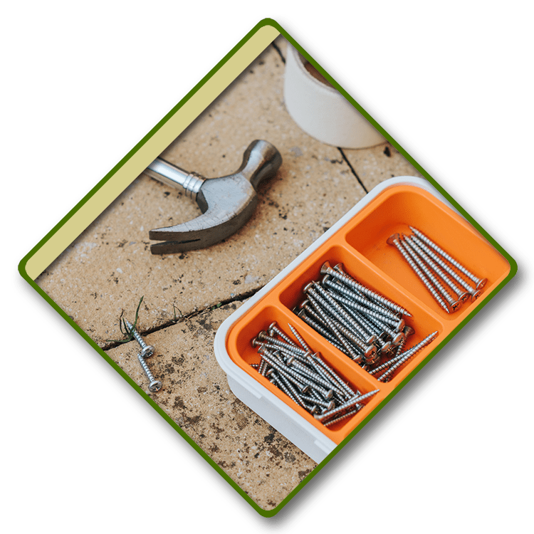 A hammer on the ground next to a tray of screws.
