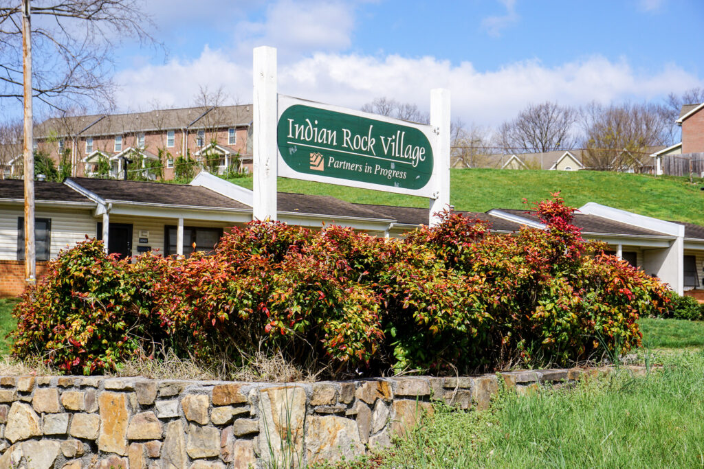 White and green sign that says Indian Rock Village.