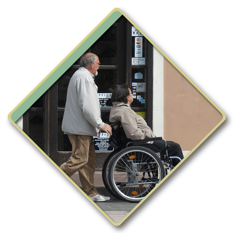 Woman in a wheelchair being pushed past a store by her caretaker.