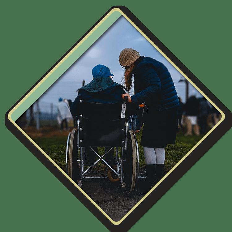 Senior citizen in a wheelchair talking to their caretaker outdoors.